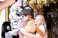 teenage couple at fun fair in close embrace