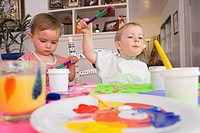 Two young two_year old girls painting with poster paints at the kitchen table & having fun Alaska United States