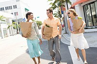 Three mid_adult friends on street holding groceries