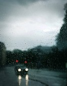 Bil med strålkastare kör på väg, vindruta täckt med regndroppar, närbild. Car With Headlights Driving On Road, Close_Up Of Windscreen Covered With Rai...