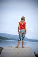 Tioårig Flicka Tittar Ut Över Sjö, Girl 10_11 Standing On Jetty, Rear View