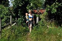 Mamma Med Son På Höften Bär Vattenhink I Grönskan På Sommarställe, Gotland., Mother Holding Son, Walking