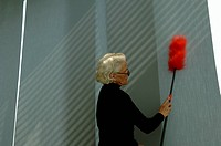 Senior woman cleaning the wall with a feather duster