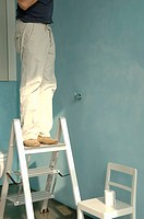 Senior man standing on a ladder in bathroom