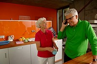 Senior couple in domestic kitchen, man phoning
