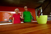 Senior couple holding hands standing in domestic kitchen
