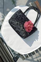 Handbag made of shiny Cloth on a Lawn Chair _ Accessory _ Textiles
