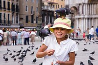Close_up of a girl feeding pigeons, St. Mark´s Square, Venice, Veneto, Italy