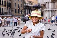 Close_up of a girl feeding pigeons, St. Mark´s Square, Venice, Veneto, Italy