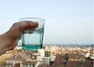 En Hand Som Håller Ett Glas Med Vatten, Human Hand Holding Glass Of Water With Buildings In The Background