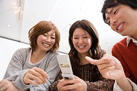 Three College Students Looking at Cellular Phone