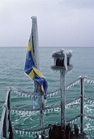 Svenska flaggan infrusen på militärfartyg. Swedish Flag On Icebound Boat In Winter