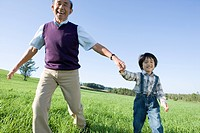 Grandfather And Grandson Running in Field