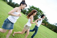 Young people smiling and running on lawn, Saipan, USA