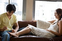 Young couple on couch, man polishing woman's toenails