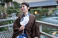 Woman in Yukata holding a Japanese fan, sitting beside the pond in garden, front view, Japan