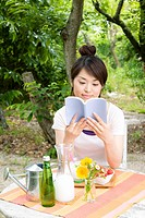 The Japanese Woman Who Reads A Book In The Shade Of A Tree