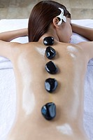 Young woman getting hot stone therapy, Saipan