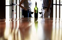 Couple standing near bottle of red wine focus on foreground (thumbnail)