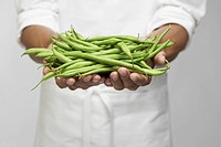 Green beans on chef's hand mid section