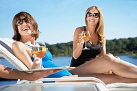 Women having drinks on lounge chairs (thumbnail)