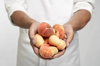 Chef holding peaches mid section