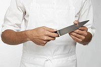 Chef holding kitchen knife mid section