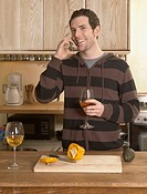 Mid_Adult Man Drinking Wine and Talking on Phone