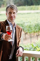 Mid adult man toasting with red wine portrait
