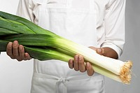 Chef holding leeks mid section
