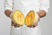 Chef holding halved cantaloupe melon mid section