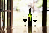 Two glasses of red wine and bottle on table