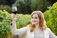 Young woman holding glass of red wine in vineyard (portrait)