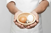 Chef holding bowl of eggs mid section