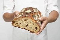 Chef holding loaf of bread mid section