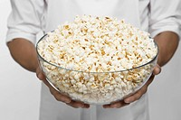 Chef holding bowl of popcorn mid section
