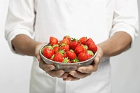 Chef holding bowl of strawberries mid section