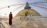 Young Buddhist monk turns to look at the dome of Boudha Bodhnath Boudhanath Tibetan stupa in Kathmandu, UNESCO World Heritage Site, Nepal, Asia