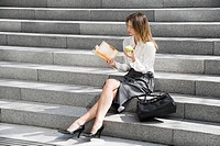Young woman reading and eating on steps (thumbnail)