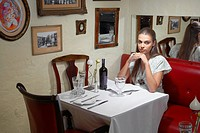 Woman sitting at dining table in restaurant (thumbnail)