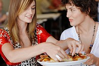 Young women eating pizza