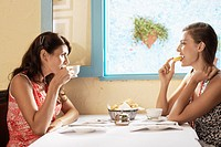 Two women eating and drinking in restaurant (thumbnail)