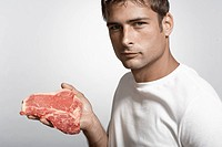 Mid adult man holding steak