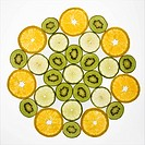 Assorted fruit slices arranged in pattern on white background.