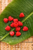 Still life of red raspberries on banana leaf