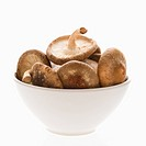 Bowlful of shiitake mushrooms on white background
