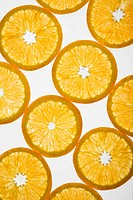 Orange slices arranged in design on white background