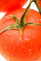 Close up of wet red ripe tomatoes against white background