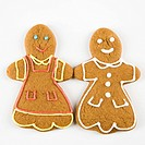 Two female gingerbread cookies holding hands