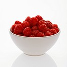Bowl of raspberries against white background